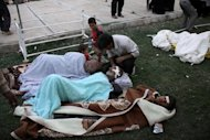 Injured Iranians lie on the grass outside a hospital in the town of Ahar, some 60 kms east of Tabriz, after a strong earthquake hit northwestern Iran