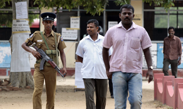 A Sri Lankan police officer stands guard as ethnic Tamil voters leave a polling station after casting their votes in Batticaloa, Sri Lanka, Saturday, Sept. 8, 2012. Sri Lankans voted Saturday in a provincial assembly election seen as a test of whether minority ethnic Tamils still want self-rule or are content with the government&#39;s development of an area devastated by a quarter-century civil war. (AP Photo/Eranga Jayawardena)