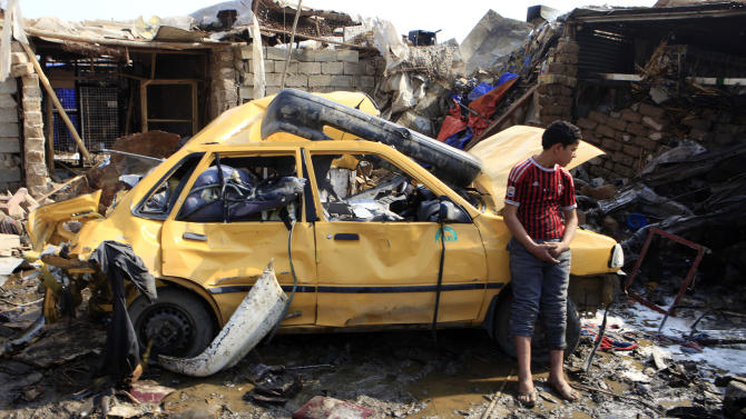 An Iraqi boy stands near a destroyed car at the scene of a car bomb attack in Baghdad's northern Kazimyah neighborhood, Friday, Feb. 8, 2013. Car bombs struck two outdoor markets in Shiite areas of Iraq on Friday, killing and wounding scores of people, police said. (AP Photo/ Karim Kadim)