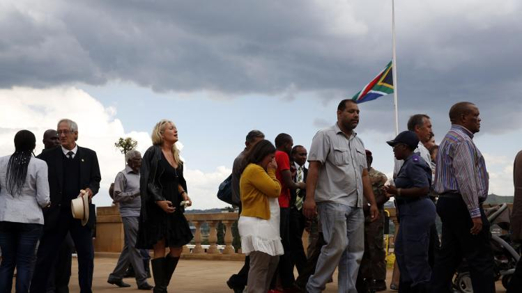 People walk away after paying their respects to former South African President Nelson Mandela on the last day of Mandela's lying in state at the Union Buildings in Pretoria