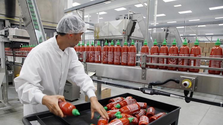 FILE - In this Oct 29, 2013 file photo, Sriracha chili sauce is produced at the Huy Fong Foods factory in Irwindale, Calif. The Commerce Department reports on wholesale prices for November on Friday, Dec. 13, 2013. (AP Photo/Nick Ut, File)