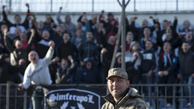 File photo of a member of the People's Militia of Crimea standing guard during a soccer match in Simferopol