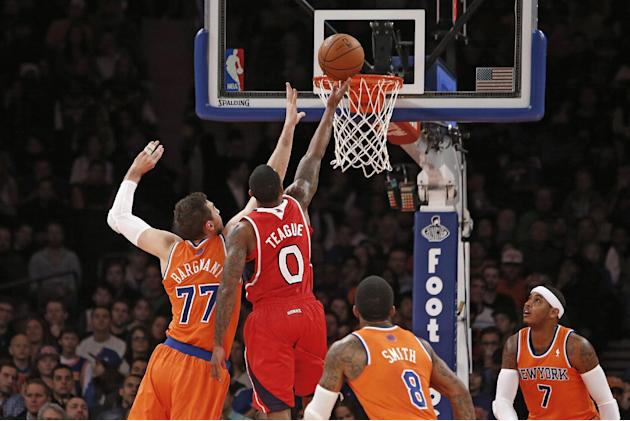 Atlanta Hawks' Jeff Teague (0) shoots against New York Knicks' Andrea Bargnani (77), of Italy, as J.R. Smith (8) and Carmelo Anthony (7) look on during the first half of an NBA basketball game Saturda