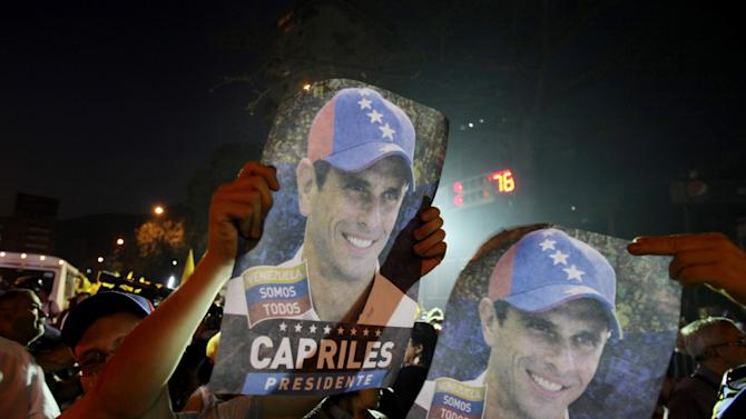 Supporters of opposition presidential candidate Henrique Capriles hold up posters of him prior to the start of a march against violence in Caracas, Venezuela, Monday, April 1, 2013. Both Nicolas Maduro, Chavez's chosen successor, and opposition Gov. Henrique Capriles face the challenge of spelling out a vision for a future without Chavez, who dominated this 28 million-person country like few other leaders have during his 14 years in power. Venezuela will hold a presidential election to replace late President Hugo Chavez on April 14. (AP Photo/Fernando Llano)