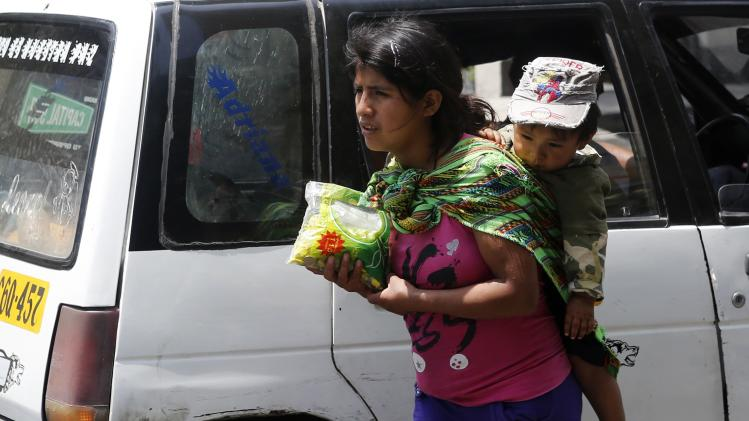 A woman carrying a baby sells candy to vehicles in Lima's San Isidro district