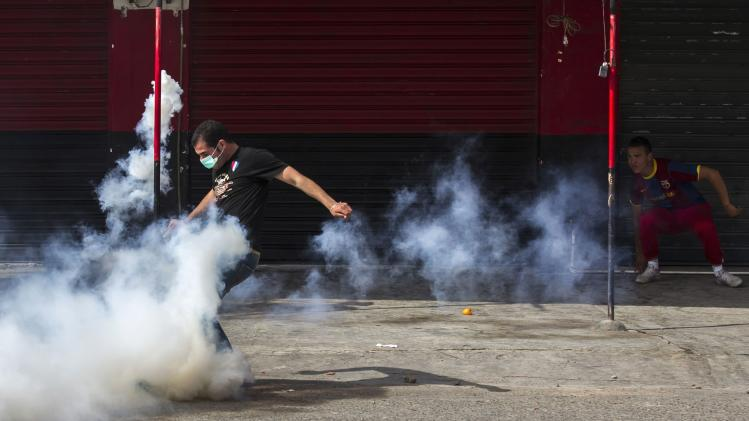 An anti-election protester kicks a tear gas canister during clashes with gendarmerie riot forces in Rafour, in the Berber region