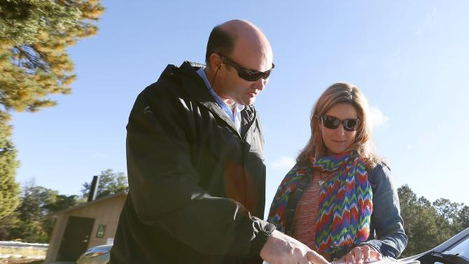 Rassie Erasmus, left, and his wife Yolanda Erasmus, of Cape Town, South Africa, look at a map to plan their next drive in an attempt to see the Grand Canyon, as the main entrance to Grand Canyon National Park remains closed to visitors due to the continued federal government shutdown on Friday Oct. 11, 2013, in Grand Canyon, Ariz.(AP Photo/Ross D. Franklin)