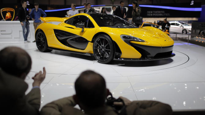 People look at the new McLaren P1 during the 83rd Geneva International Motor Show, Switzerland, Monday, March 4, 2013. The Motor Show will open its gates to the public from March 7 to 17.  (AP Photo/Laurent Cipriani)