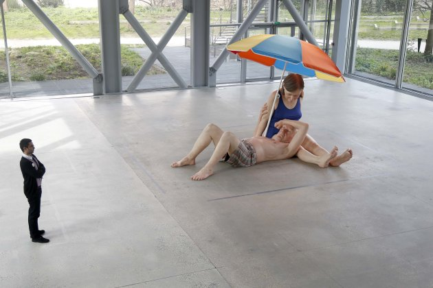 "An employee looks at a sculpture entitled ""Couple Under an Umbrella, 2013"" by artist Ron Mueck during his exhibition at the Fondation Cartier pour l'art contemporain in Paris"