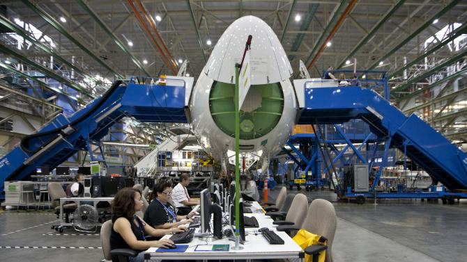 Workers on the floor in front of a Boeing Co. 787 on the assembly line in Everett, Wash. on Sunday, Sept. 25, 2011. All Nippon Airways is the first customer to take delivery of the 787. (AP Photo/John Froschauer)