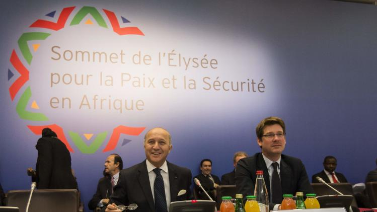 French Foreign Affairs Minister Fabius and French Junior Minister for Foreign Countries and Development, Pascal Canfin (R) attend a ministerial meeting as part of the Elysee Summit for Peace and Security in Africa, held in Paris