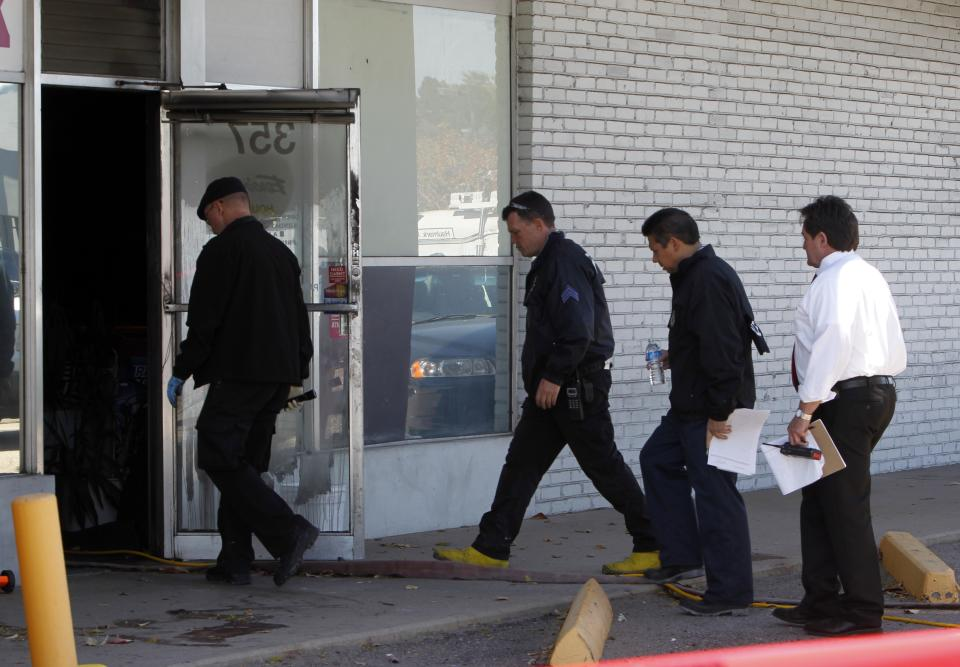 Police investigators walk into Fero's Bar and Grill in Denver on Wednesday, Oct. 17, 2012, where the bodies of a man and four woman were discovered after firefighters extinguished a fire at the bar early Wednesday morning. Police think the blaze was set to cover up their slayings. (AP Photo/Ed Andrieski)