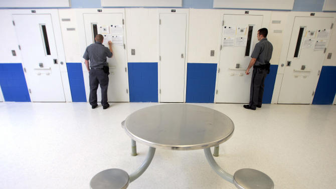 FILE - In this Thursday, May 31, 2007 file photo, Juvenile Corrections Officers Robert Zinn, left, and Nathan Castle, right, look in on prisoners in their solitary confinement cells and fill out a log of check times at the Marion Juvenile Corrections Institute in Marion, Ohio. Each of the inmates needs to be checked on every 15 minutes by the officers while in confinement. In a report released Wednesday, Oct. 10, 2012, two of the nation's leading advocates for prisoners' rights said state governments should abolish the use of solitary confinement for offenders under 18, whether as a punitive or protective measure. (AP Photo/Columbus Dispatch, James D. DeCamp)