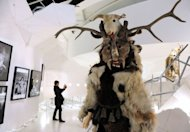 "Visitors look at masks and outfits on display during the exhibition ""Les maitres du desordre"" (The masters of disorder) on April 10 at the Quai Branly Museum in Paris. Until July 29, the museum on the banks of the Seine is showcasing more than 300 ethnological objects alongside two dozen contemporary artists, among them US giants like Paul McCarthy or the late Jean-Michel Basquiat"