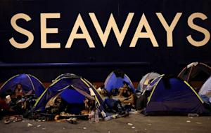 Migrants and refugees camp in the port at the Greek…