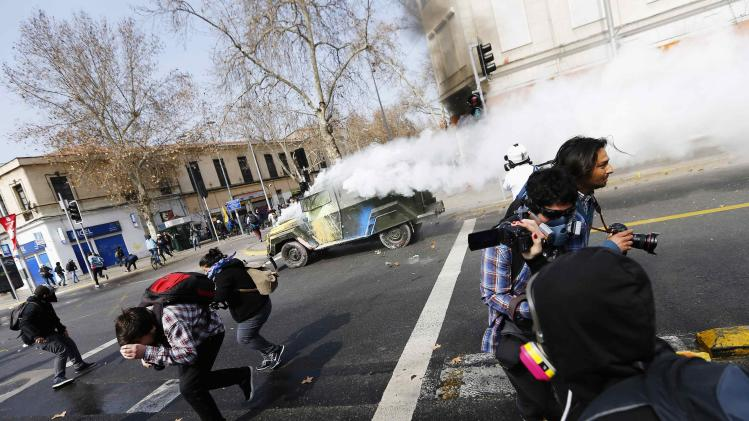 A riot police vehicle releases tear gas during demonstration against government to demand changes in education system in Santiago