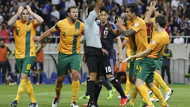 Australia's Matthew Mckay (R) is given a yellow card as Japan is awarded a penalty kick during their 2014 World Cup qualifying match in Saitama (Reuters)