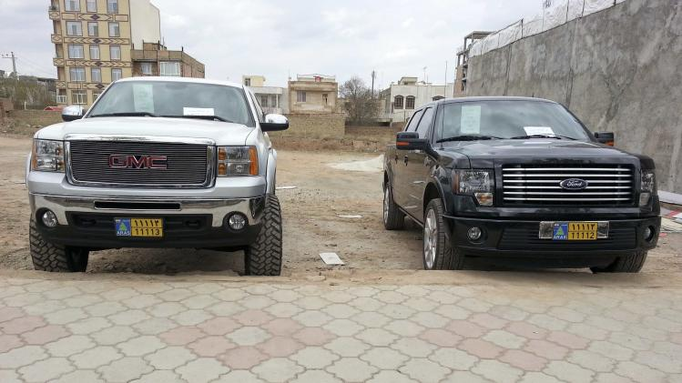 Handout shows a 2013 Ford F-150 special edition truck and a GMC truck outside an auto dealership in Aras free zone in northwest Iran