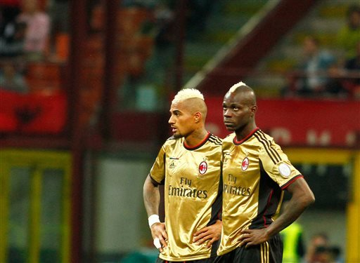In this Sunday May 12, 2013, file photo, AC Milan players Kevin Prince Boateng, left, and Mario Balotelli look toward the stands during a stoppage in play in a Serie A soccer match between AC Milan an