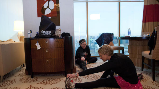 In this photo taken Sunday, Dec. 4, 2011, Rachel Midgett of Houston, Texas, foreground, stretches with Heather Keister of Lubbock, Texas before heading to the start line to run in the half marathon of the Las Vegas Marathon, in Las Vegas. Afflicted with breast cancer, Midgett has been taking the drug Afinitor for the last nine months and said that the cancer has not progressed in that time period, longer than other cancer drugs she has taken in the past. (AP Photo/Julie Jacobson)
