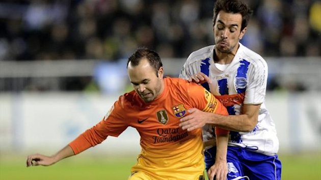 Barcelona's Andres Iniesta fights for the ball with Deportivo Alaves player Guzman Casaseca during their Copa del Rey match at Mendizorroza stadium (Reuters)