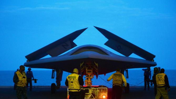 In this image provided by the U.S. Navy an X-47B Unmanned Combat Air System demonstrator is towed Monday, May 13, 2013 into the hangar bay of the aircraft carrier USS George H.W. Bush. The carrier is scheduled to be the first aircraft carrier to catapult-launch an unmanned aircraft from its flight deck Tuesday May 14, 2013. (U.S. Navy photo by Mass Communication  (AP Photo/US Navy, Specialist 2nd Class Timothy Walter)