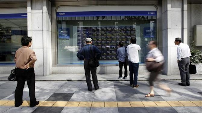 Pedestrians look at a stock quotation board displaying various stock prices outside a brokerage in Tokyo October 11, 2013. REUTERS/Yuya Shino/Files