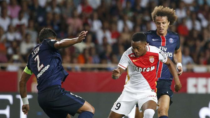 Monaco's Martial challenges Paris St Germain's Da Silva and Luiz during their Ligue 1 soccer match at Louis II stadium in Monaco