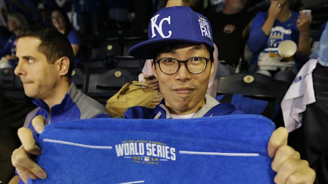 Kansas City Royals fan Sung Woo Lee, from South Korea, shows off a World Series towel before Game 1 of baseball's World Series between the Kansas City Royals and the San Francisco Giants Tuesday, Oct. 21, 2014, in Kansas City, Mo. (AP Photo/Charlie Neibergall)