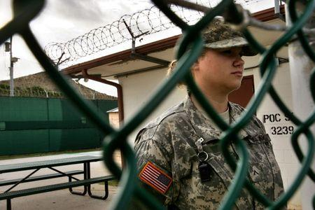 In this photo reviewed by U.S. military officials, a U.S. soldier guards a gate within the compound ..