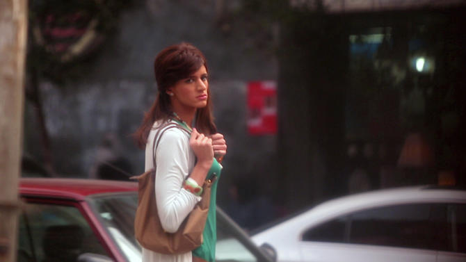 """In this undated image made from video released by the producers of """"Awel el Kheit"""" or """"the Thread"""" which airs on the private TV station ONTV, Waleed Hammad walks in a busy shopping district in Cairo, Egypt, dressed as a woman as a hidden camera crew films him for an investigative story on sexual harassment. The 24-year-old actor dressed conservatively for his mission into the secret world of sexual harassment and abuse on the streets of Cairo, donning a long skirt and sleeved shirt and covering his head like many Egyptian women.(AP Photo)"""