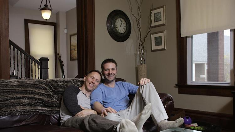 """In this Nov. 16, 2011 photo, Capt. Stephen Hill, left, and his partner, Joshua Snyder, pose for a photo in their home in Columbus, Ohio. Hill, the U.S. Army captain who was booed during a Republican presidential debate when he asked a question about """"don't ask, don't tell,"""" just returned from a year-long deployment in Iraq, and says he wasn't trying to score political points, just peace of mind for himself and his husband of four-and-a-half months. (AP Photo/Jay LaPrete)"""