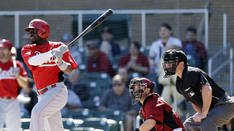 Cincinnati Reds' Brandon Phillips, left, singles against the Arizona Diamondbacks during the first inning of an exhibition spring training baseball game on Wednesday, Feb. 27, 2013, in Scottsdale. Ariz. (AP Photo/Marcio Jose Sanchez)