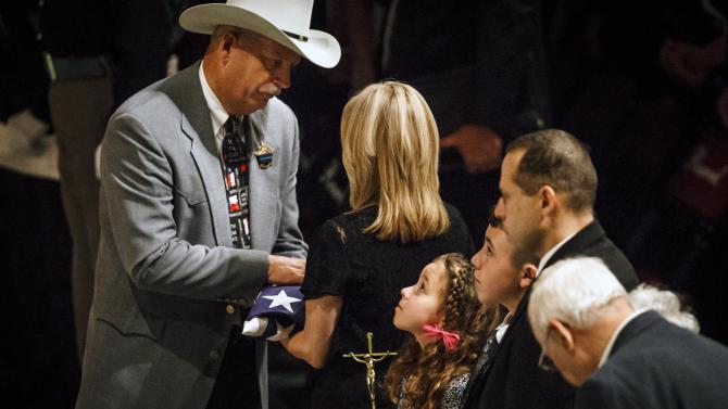 Brazos County Sheriff Chris Kirk, left to right, gives a flag to Donna Bachmann as her daughter Caitlyn Bachmann looks on during the funeral service for her husband Brazos County Precinct 1 Constable Brian Bachmann  at Reed Arena on the Texas A&M University Campus, Saturday, Aug. 18, 2012, in College Station, Texas.  Bachmann was fatally shot while trying to serve a court summons for being two months behind on rent.  (AP Photo/Houston Chronicle, Michael Paulsen) MANDATORY CREDIT:  MICHAEL PAULSEN/HOUSTON CHRONICLE