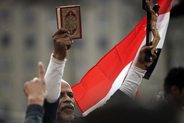 An Egyptian protester holds up a Koran and a figure of Christ on the cross during a demonstration against President Mohamed Morsi's decree granting himself broad powers in Cairo's Tahrir Square on Nov