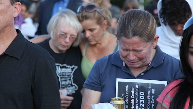 """People mourn at a vigil, Friday, July 20, 2012 in Aurora, Colo. Authorities report that 12 died and more than three dozen people were shot during an assault at the theatre during a midnight premiere of """"The Dark Knight."""" (AP Photo/Robert Ray)"""