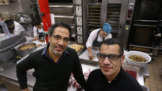 In this Tuesday, Dec. 18, 2012 photo, chefs Yotam Ottolenghi, left, and Sami Tamimi, right, pose for the photographer at their company's bakery in London. One chef is Israeli, the other a Palestinian. So it is with 'Jerusalem' their latest cookbook, that traces their memories of a shared city, the Jewish west and the Arab east, together with the food_ the commodity held in common in a city riven by division. Ottolenghi and Tamimi who have been business partners for about 10 years, run two restaurants and three delis in London and wrote their first cookbook four years ago. They were simply known for saving London's chicest neighborhoods from culinary boredom with Mediterranean-based recipes infused with exotic flavors.  Their new book 'Jerusalem' explores  the cuisine of the ancient city. (AP Photo/Lefteris Pitarakis)