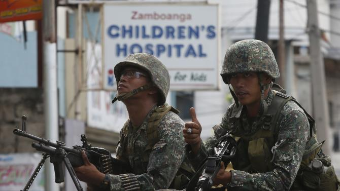 Members of the Philippine marines hold their weapons aboard a truck as they block a road during fighting between government soldiers and Muslim rebels of MNLF in Zamboanga city, southern Philippines