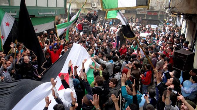 "In this citizen journalism image provided by Aleppo Media Center AMC which has been authenticated based on its contents and other AP reporting, anti-Syrian regime protesters raise up their hands as they wave  Syrian revolutionary flags during a protest to mark the second anniversary of the their uprising, in Aleppo, Syria, Friday March 15, 2013. The chief of Syria's main, western-backed rebel group marked the second anniversary of the start of the uprising against President Bashar Assad on Friday by pledging to fight until the ""criminal"" regime is gone. (AP Photo/Aleppo Media Center, AMC)"