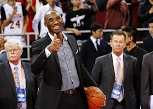Los Angeles Lakers' Bryant gestures to his teammates before their game against the Golden State Warriors at the NBA Global Games in Beijing