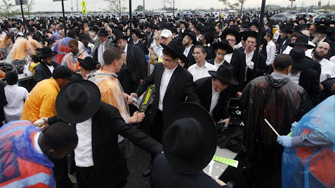A large crowd of Orthodox Jewish men wait to be checked by security at MetLife stadium in East Rutherford, N.J, Wednesday, Aug. 1, 2012, as they arrive for the start of the celebration Siyum HaShas. The Siyum HaShas, marks the completion of the Daf Yomi, or daily reading and study of one page of the 2,711 page book. The cycle takes about 7½ years to finish. This is the 12th put on by Agudath Israel of America, an Orthodox Jewish organization based in New York. Organizers say this year's will be, by far, the largest one yet. More than 90,000 tickets have been sold, and faithful will gather at about 100 locations worldwide to watch the celebration. (AP Photo/Mel Evans)