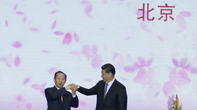 Chinese President Xi Jinping holds hands with the chairman of Japan's LDP's General Council Toshihiro Nikai during the China-Japan friendship exchange meeting at the Great Hall of the People in Beijing