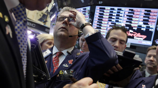 Trader John Panin, second left, adjusts his glasses as he works on the floor of the New York Stock Exchange Thursday, May 23, 2013. A global stock market slump is continuing on Wall Street as traders worry about how committed the Federal Reserve remains to keeping up its bond-buying program. (AP Photo/Richard Drew)