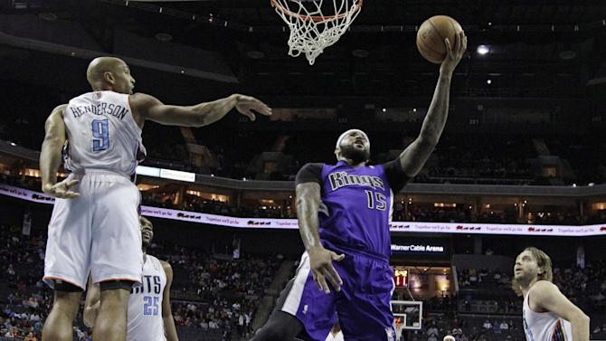 Sacramento Kings' DeMarcus Cousins, center, shoots between Charlotte Bobcats' Gerald Henderson, left, and Josh McRoberts, right, during the first half of an NBA basketball game in Charlotte, N.C., Tuesday, Dec. 17, 2013
