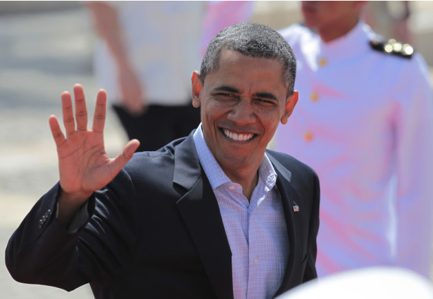 President Barack Obama waves as he arrives at the Convention Center for the second working session of the sixth Summit of the Americas in Cartagena, Colombia, Sunday April 15, 2012. (AP Photo/Fernando