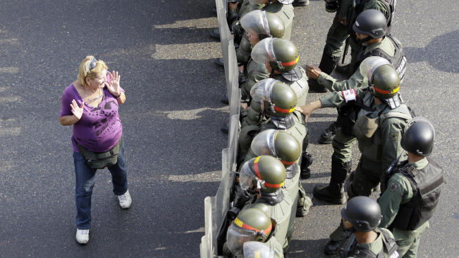 An opposition supporter walks by a line of riot police along a highway in the Altamira neighborhood of Caracas, Venezuela, Monday, April 15, 2013. The opposition is protesting the official results in Venezuela's disputed Sunday presidential election. Opposition candidate Henrique Capriles has challenged his narrow loss to Nicolas Maduro and is demanding a recount. (AP Photo/Fernando Llano)