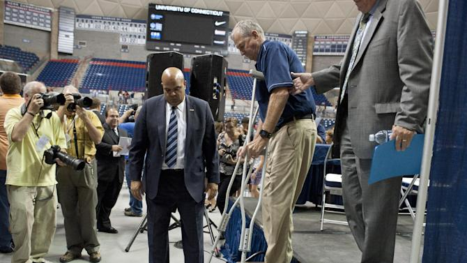 Retired Connecticut head coach Jim Calhoun, using crutches, is helped down the stairs of the stage after a news conference, Thursday, Sept. 13, 2012, in Storrs, Conn. Calhoun, who built Connecticut into a basketball power and coached the Huskies to three national titles, announced his retirement Thursday. He fractured his hip last month and needs crutches to help him walk. (AP Photo/Jessica Hill)