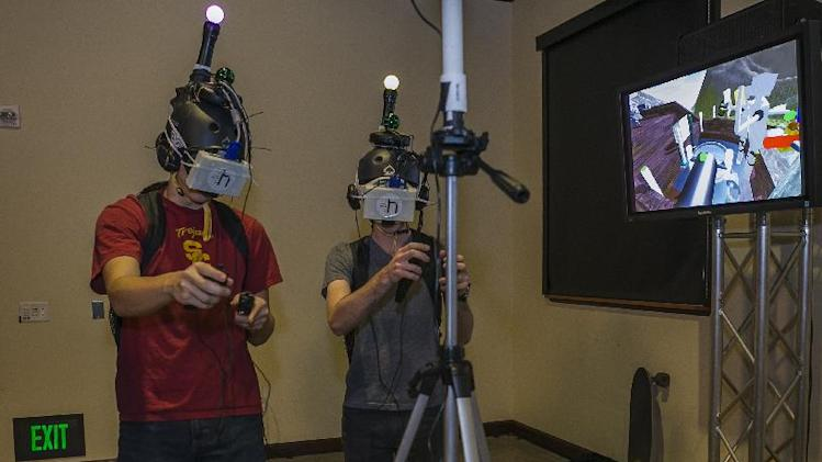 In this photo taken Tuesday, Jan. 29, 2013, University of Southern California, USC Institute for Creative Technologies computer students: Travis Primm, left, and Aaron Hoogstraten interact with Project Holodeck, a virtual reality gaming platform at the Glimpse virtual technology showcase at the USC campus in Los Angeles.(AP Photo/Damian Dovarganes)