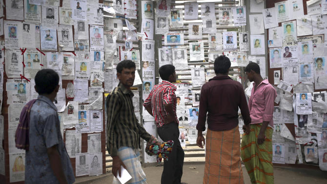 """People look at portraits of missing garment workers from the collapse of a garment factory building plastered on the doors of a school-turned-morgue Saturday, May 4, 2013 in Savar, near Dhaka, Bangladesh. The death toll in the accident rose to more than 530 on Saturday, a day after the country's finance minister downplayed the impact of the disaster on the garment industry, saying he didn't think it was """"really serious."""" (AP Photo/Wong Maye-E)"""