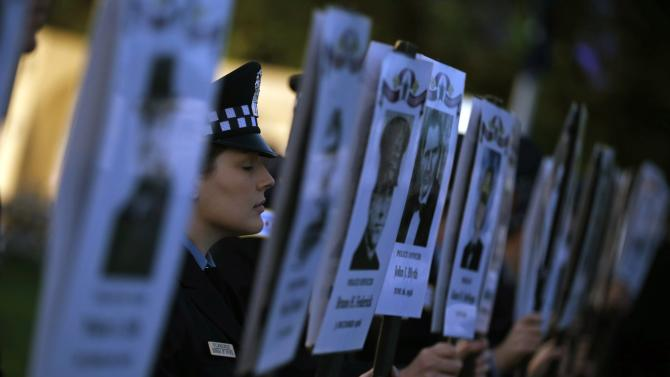 Chicago Police officers hold photographs of officers killed in the line of duty at the 11th Annual Chicago Police Memorial Foundation's Candlelight Vigil in Chicago